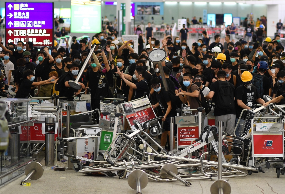 Pro-democracy protestors block the entrance to the airport terminals after a scuffle with police at Hong Kong's international airport late on August 13, 2019. - Hundreds of flights were cancelled or suspended at Hong Kong's airport on August 13, 2019 as pro-democracy protesters staged a second disruptive sit-in at the sprawling complex, defying warnings from the city's leader who said they were heading down a