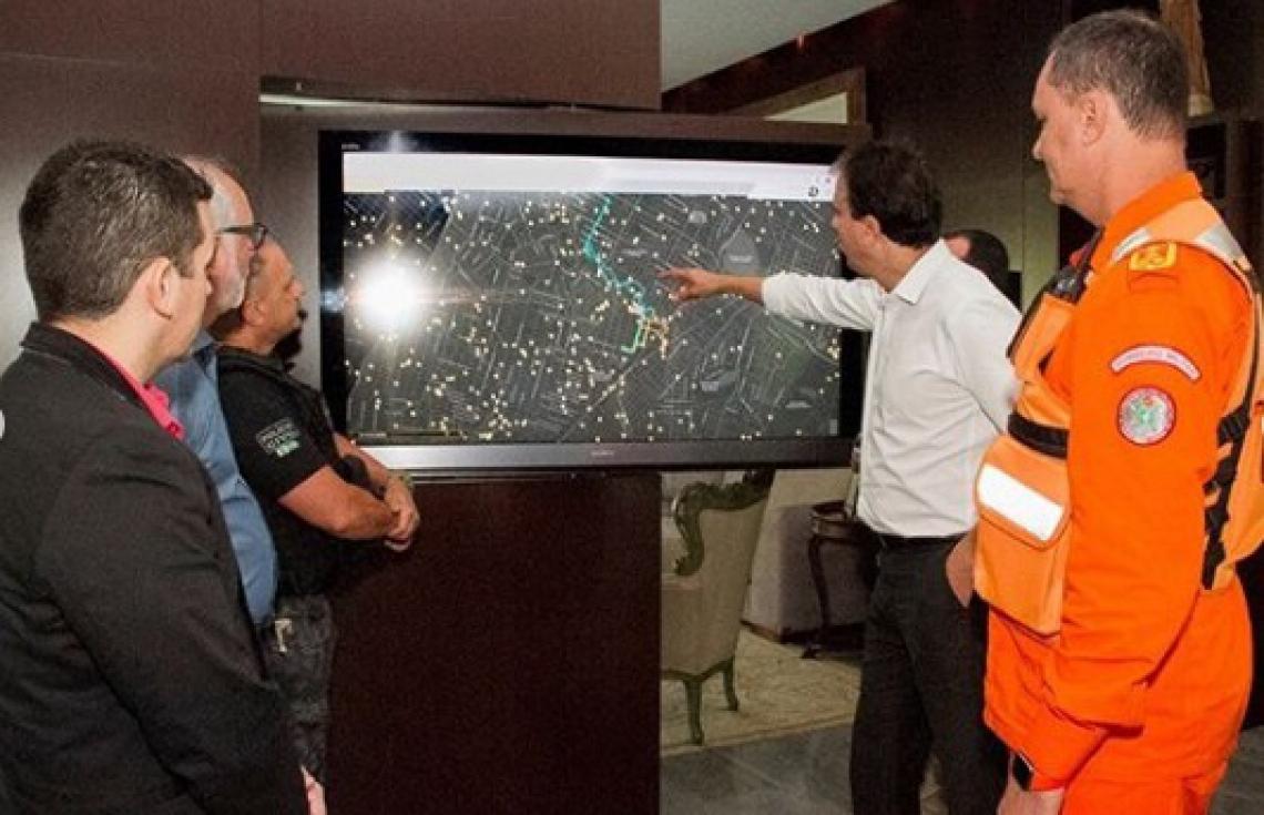Camilo observa telas  de monitoramento ao lado  de gestores da segurança  e sistema prisional