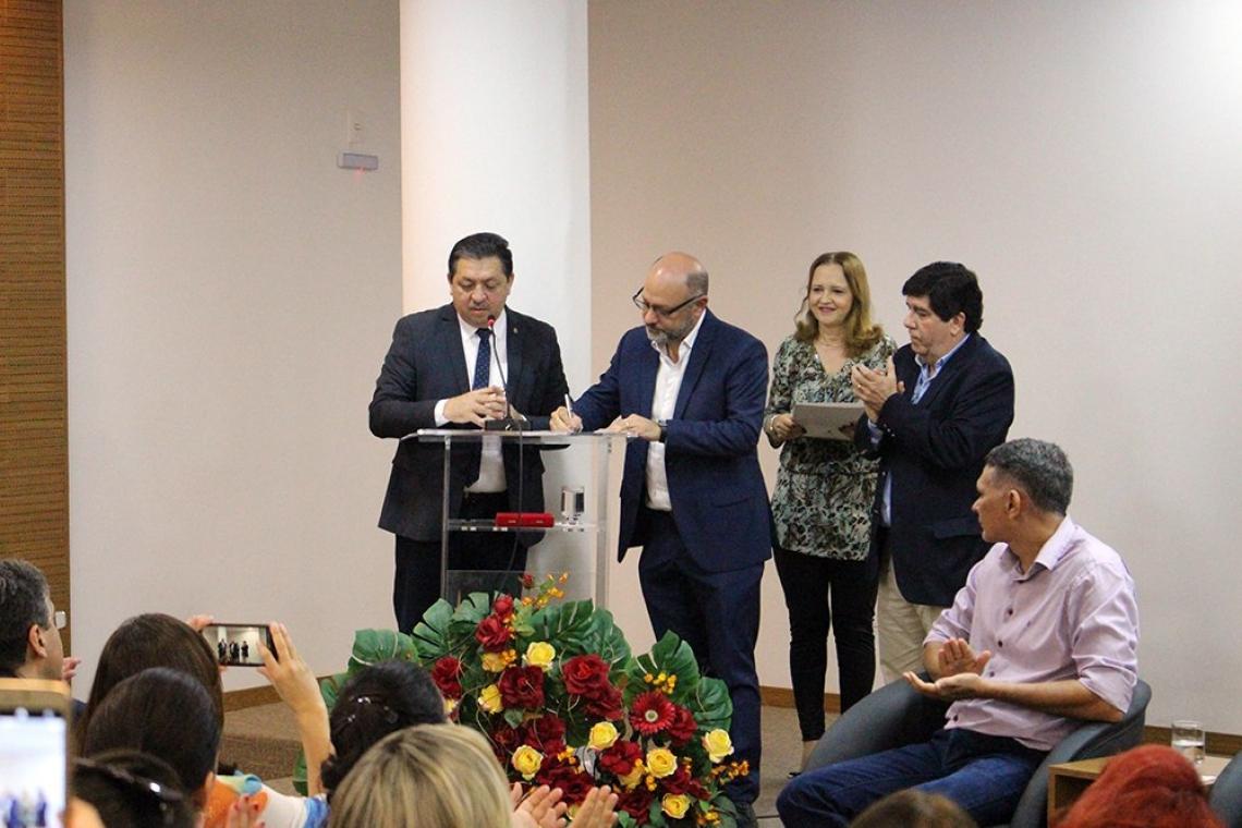 Novo superintendente da Escola de Saúde Pública, Marcelo Alcantara Holanda promete interiorizar o atendimento. Ele assina, na imagem o termo de posse. Foto: Divulgação