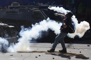 Manifestantes entram em choque com a polícia durante um protesto em Santiago, Chile, em 21 de outubro de 2019. - O Chile ordenou um toque de recolher durante a noite pelo terceiro dia consecutivo na segunda-feira, enquanto as violentas manifestações e saques que deixaram 11 pessoas mortas continuaram pelo quarto dia consecutivo. . (Foto de CLAUDIO REYES / AFP)