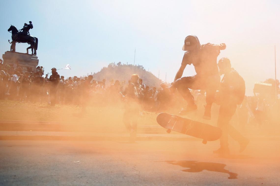 """Pessoas protestam na praça Italia em Santiago, Chile, em 21 de outubro de 2019. - O número de mortos no Chile subiu para 11, disseram autoridades na segunda-feira, depois de três dias de violentas manifestações e saques que viram o presidente Sebastian Pinera alegando que o país estava """"em guerra."""" (Foto de Pablo VERA / AFP)"""