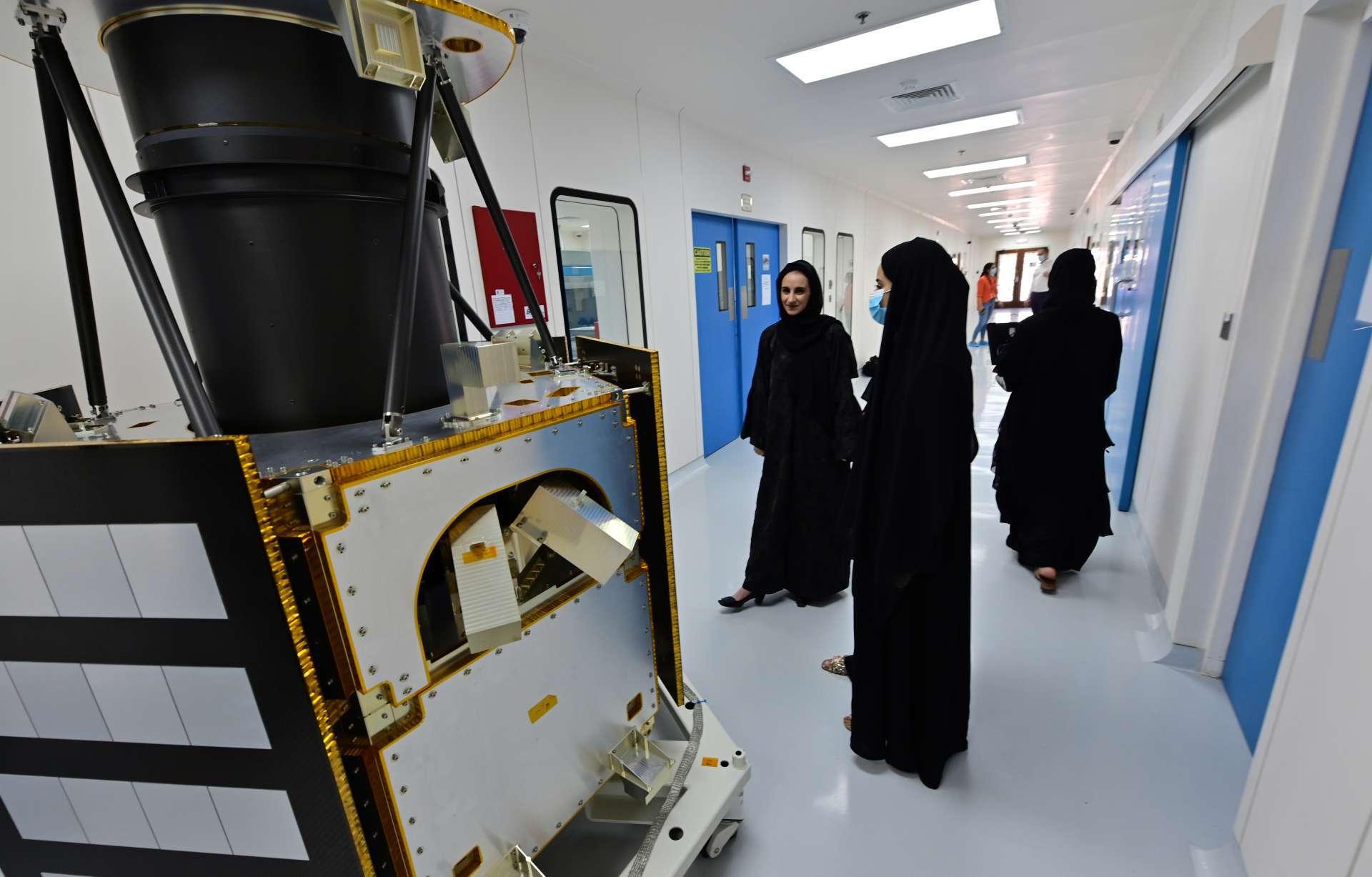 Engenheiros se reúnem em frente a um modelo KhalifaSat no Centro Espacial Mohammed Bin Rashid (MBRSC), na cidade do Golfo de Dubai
