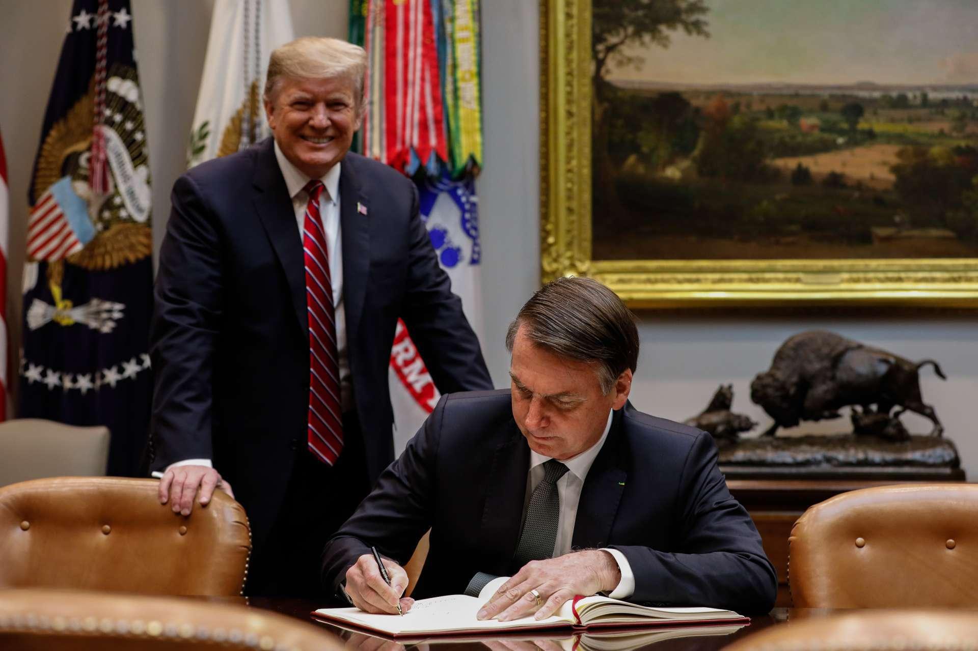 Recebido por Donald Trump, Jair Bolsonaro assina o livro de visitas da Casa Branca em março de 2019, na primeira visita oficial dele como presidente aos Estados Unidos