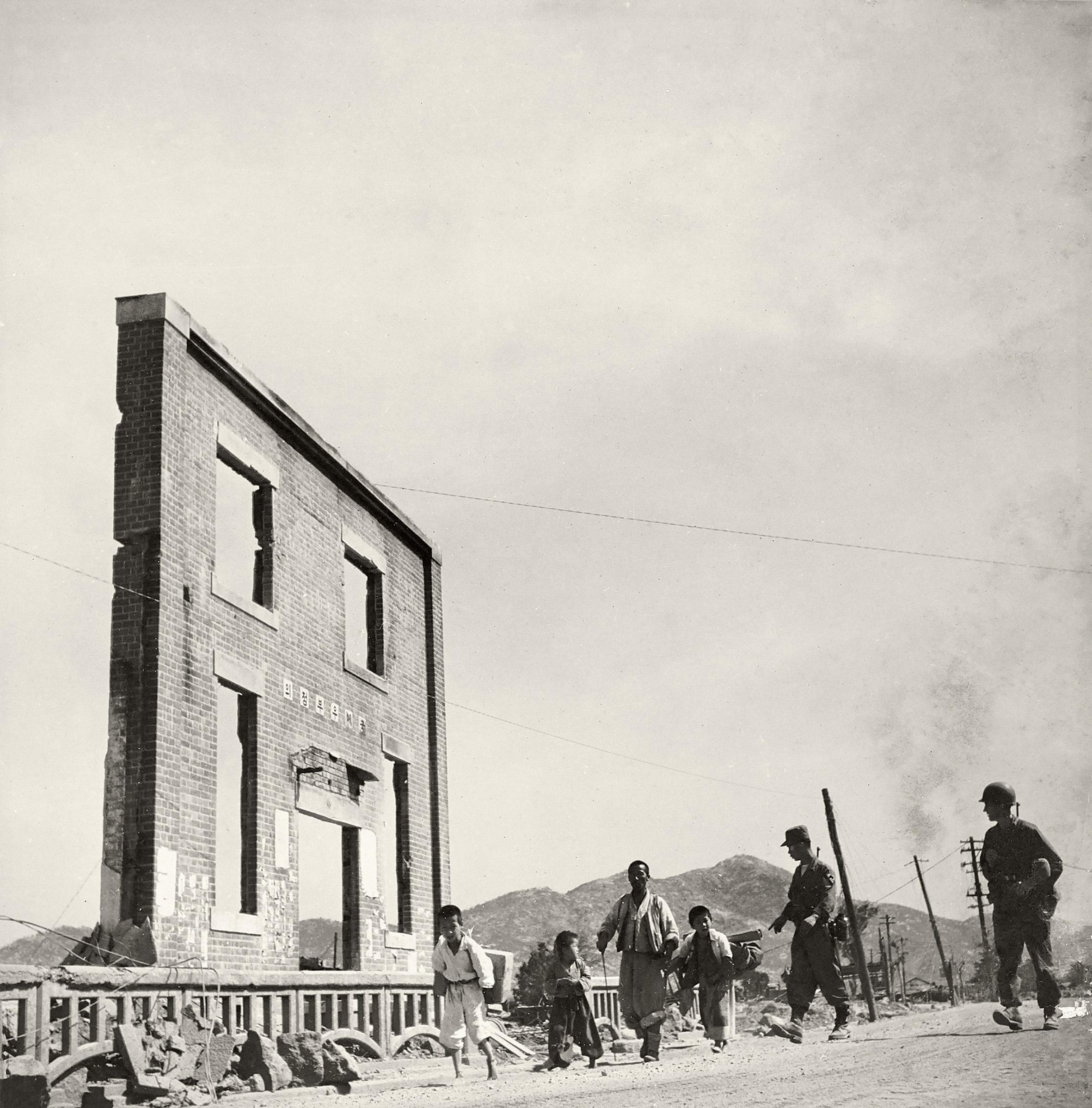 Refugiados e soldados norte-americanos em Seul após a retomada da cidade. Seul, Coreia do Sul, março de 1951
