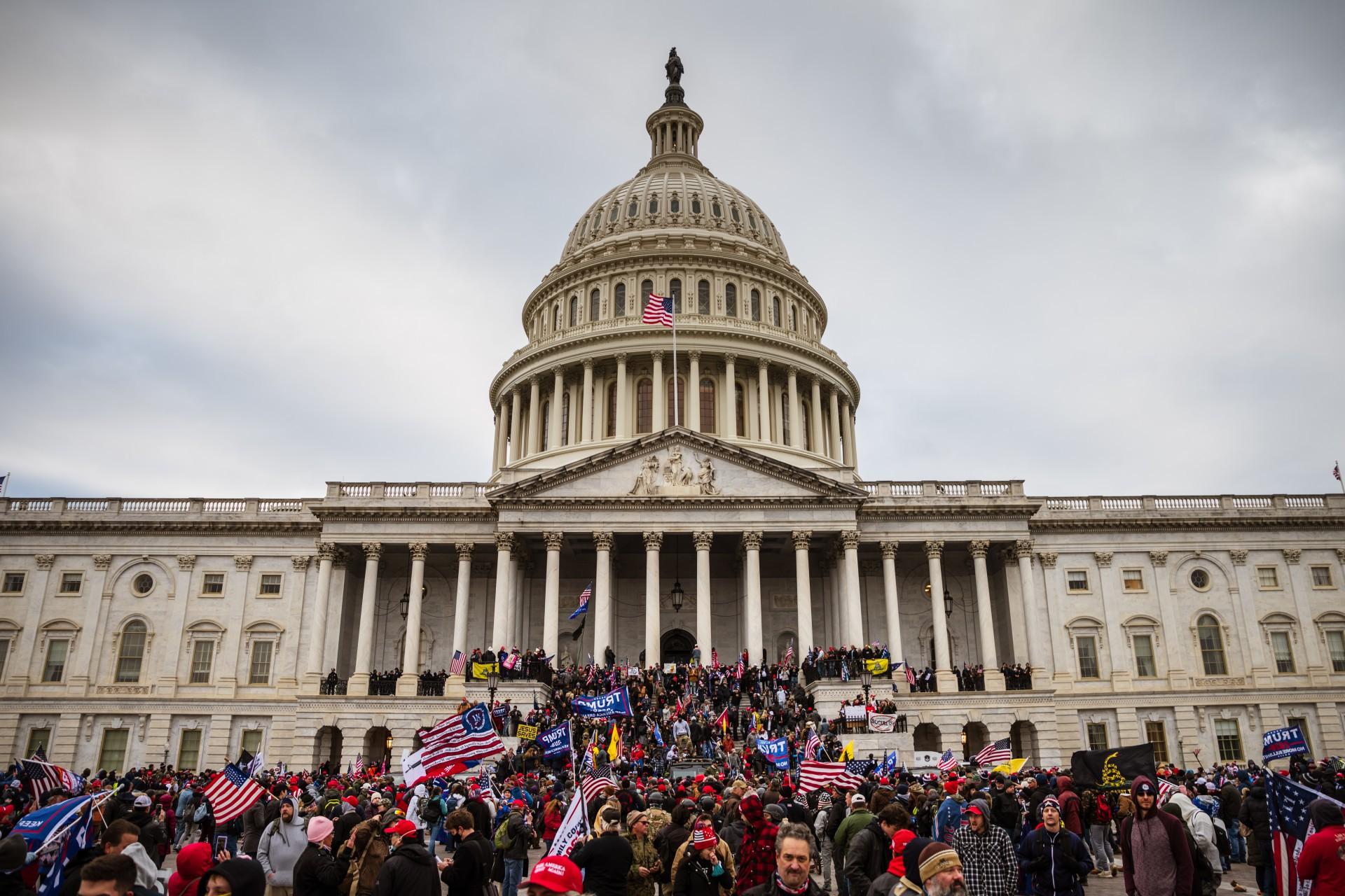 WASHINGTON, DC - 06 de janeiro: Um grande grupo de manifestantes pró-Trump fica na escadaria leste do edifício do Capitólio depois de invadir suas terras em 6 de janeiro de 2021 em Washington, DC. Uma multidão pró-Trump invadiu o Capitol, quebrando janelas e entrando em confronto com policiais. Os apoiadores de Trump se reuniram na capital do país hoje para protestar contra a ratificação da vitória do Colégio Eleitoral do presidente eleito Joe Biden sobre o presidente Trump nas eleições de 2020. Jon Cherry / Getty Images / AFP  (Foto: AFP)