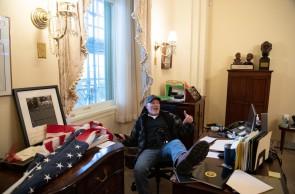 Um apoiador do presidente dos EUA, Donald Trump, está sentado no escritório da presidente da Câmara dos EUA, Nancy Pelosi, enquanto ele protesta dentro do Capitólio dos EUA em Washington, DC, 6 de janeiro de 2021. - Manifestantes violaram a segurança e entraram no Capitólio enquanto o Congresso debatia o a 2020 Eleição presidencial de voto eleitoral. (Foto de SAUL LOEB / AFP)