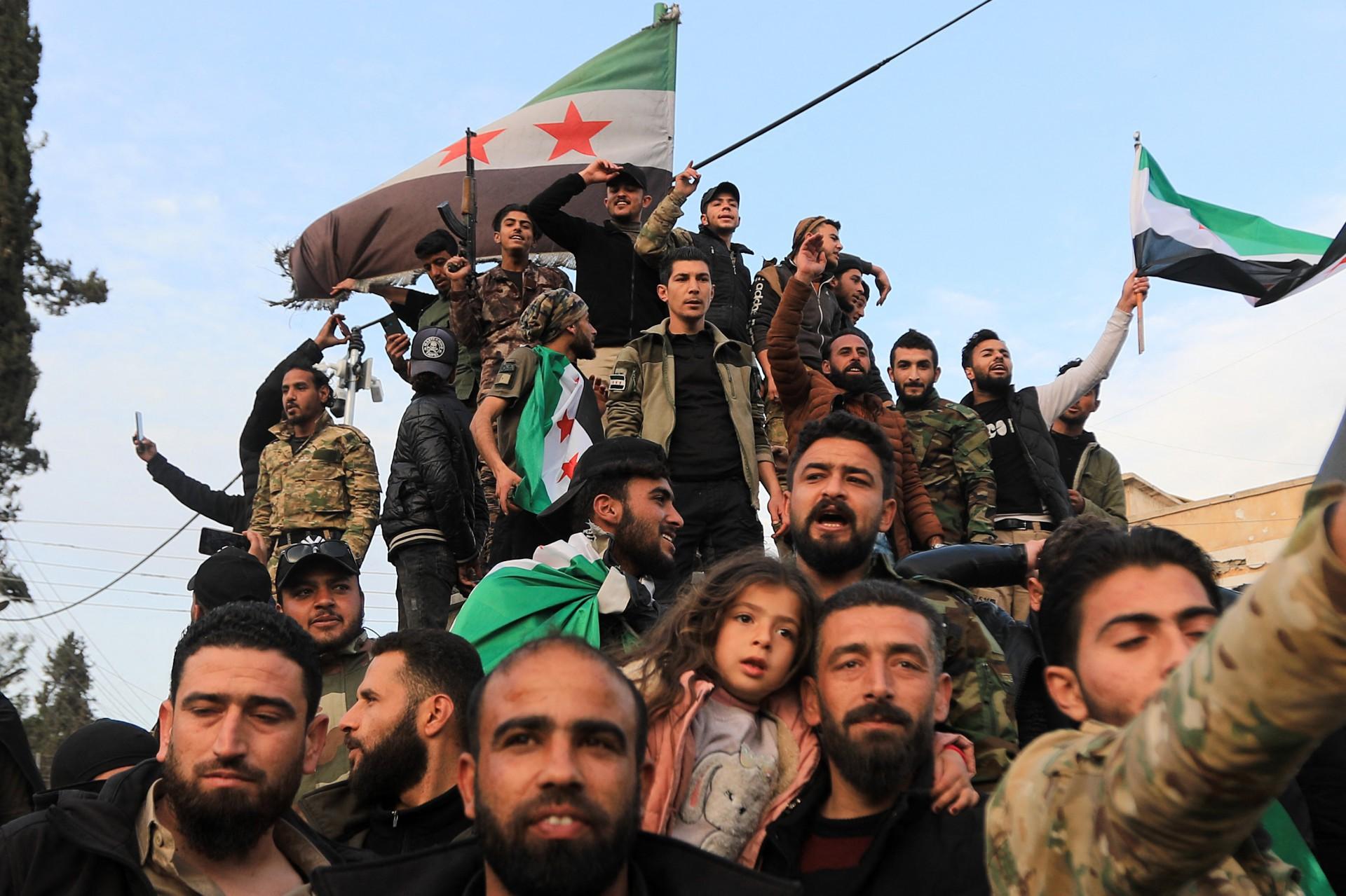 Combatentes sírios ao lado dos turcos que os apoiam na guerra que já completa uma década. Na fotos, eles se reúnem em Raqa, norte da Síria.