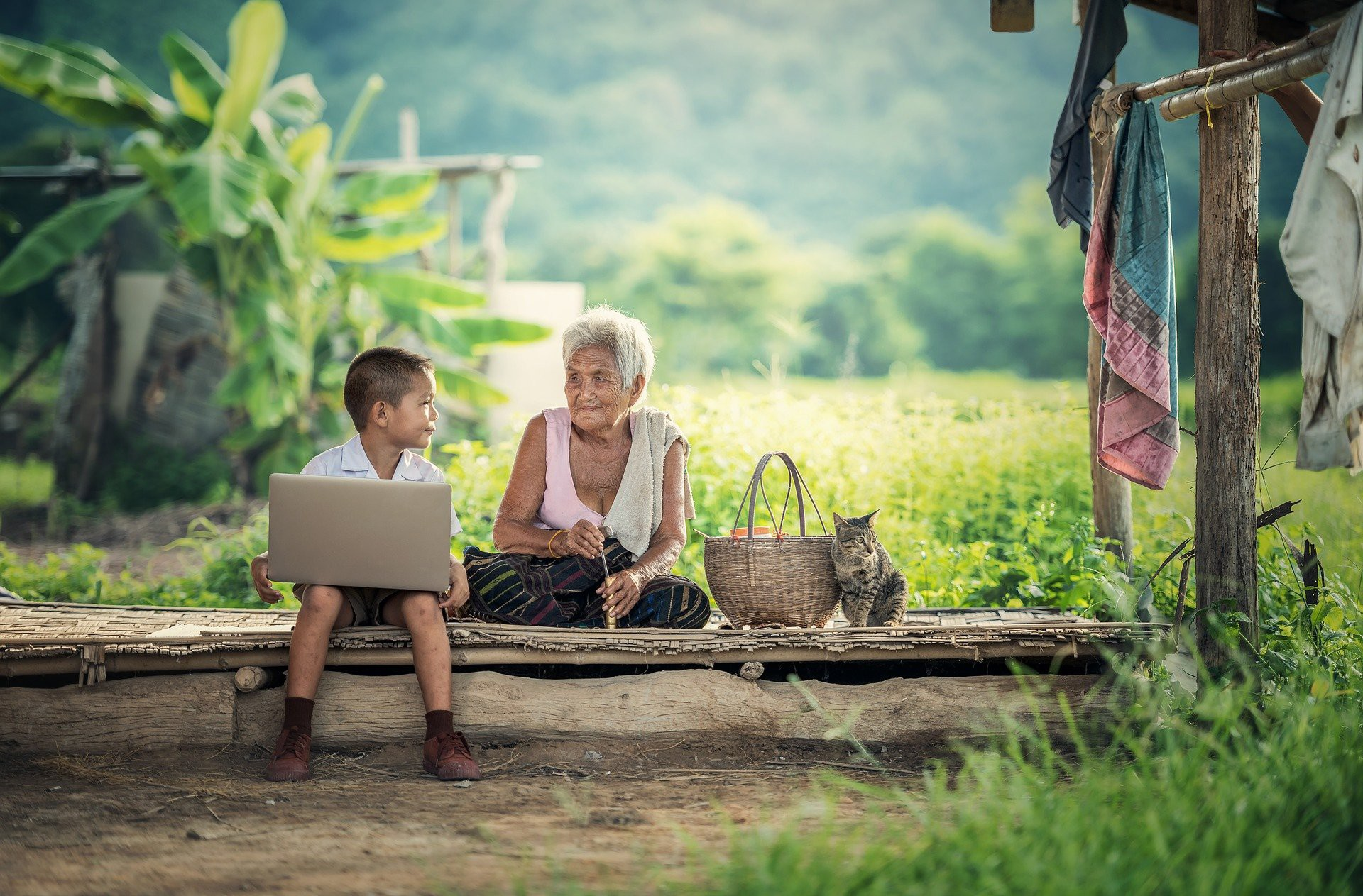 Neto e avó conversam enquanto ele usa laptop