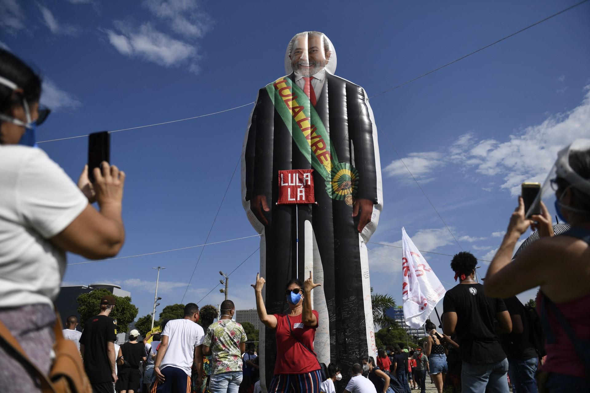 Uma mulher posa para uma foto com um manequim retratando o ex-presidente brasileiro (2003-2011) Luiz Inácio Lula da Silva com uma faixa lendo Lula Livre durante um protesto contra a forma como o presidente Jair Bolsonaro lidou com a pandemia de COVID-19 no centro do Rio de Janeiro, Brasil em 29 de maio de 2021. (Foto: MAURO PIMENTEL / AFP)