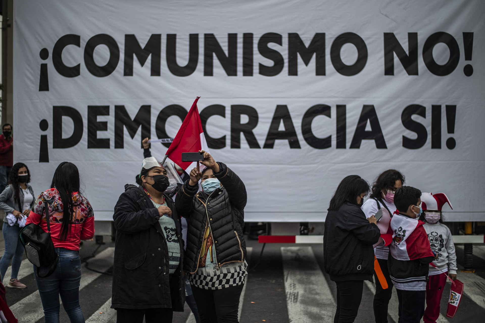 """Apoiadores do candidato peruano pelo Partido Popular Fuerza, Keiko Fujimori, protestam em frente ao prédio do Organismo Nacional de Processos Eleitorais (ONPE) em Lima, no dia 09 de junho de 2021. - O sindicalista de extrema esquerda Pedro Castillo se elegeu como vencedor da eleição presidencial do Peru, agradecendo as nações estrangeiras pelas mensagens de """"vitória"""", mesmo com as autoridades eleitorais dizendo na quarta-feira que a disputa não havia terminado. Com mais de 98 por cento dos votos expressos na votação presidencial de domingo contados na manhã de quarta-feira, Castillo manteve a pontuação de liderança de 50,2 por cento sobre 49,7 por cento do rival populista de direita Keiko Fujimori. (Foto de Ernesto BENAVIDES / AFP)"""
