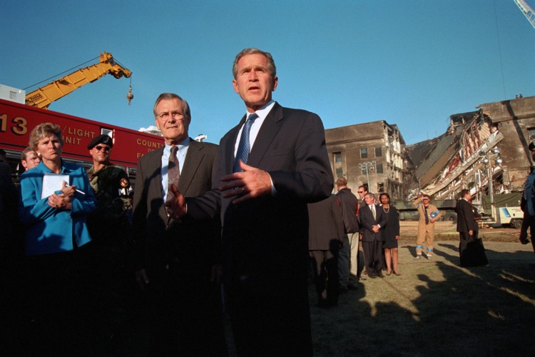 O presidente George W. Bush discursa em frente ao Pentágono danificado em Arlington, Virgínia. O presidente está acompanhado por Karen Hughes, conselheira do presidente, e secretário de Defesa Donald Rumsfeld.(Foto: Eric Draper/Casa Branca)